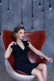 Beautiful brunette in a black dress sits claret chair Stock Photos