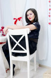 Beautiful brunette in a black dress. Sitting on a chair Stock Photos