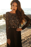 Beautiful brunette in black lace dress posing on beach Royalty Free Stock Photos