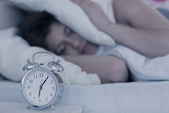 Beautiful brunette blocking the noise from alarm clock in her bed Royalty Free Stock Photography
