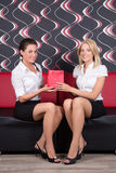 Beautiful brunette and blond sitting on the sofa with present Royalty Free Stock Images
