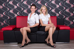 Beautiful brunette and blond sitting on the sofa Royalty Free Stock Images
