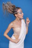 Beautiful brunette blonde young skiny woman in greece mythology. Styled outfit white toga and creative abstract hairstyle and creative make up on a neutral blue Stock Photo