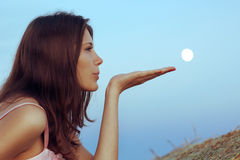 Beautiful brunette blows the moon with palm. Close-up stock photos