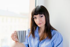 A beautiful brunette in blue shirt drinking he first morning cup of coffee or tea Royalty Free Stock Images