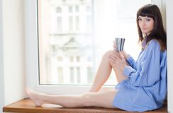 Beautiful brunette in a blue shirt sitting on the windowsill, and drinking coffee Royalty Free Stock Photography