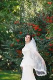 Beautiful brunette bride with bouquet outdoor. Happy bride outdo royalty free stock photo