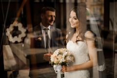 Bride looks out the window at the reflection of groom. Beautiful brunette bride in a dress and a bouquet of roses looks out the window at the reflection of her royalty free stock images