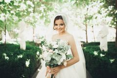 Beautiful brunette bride in elegant white dress holding bouquet posing neat trees Stock Image
