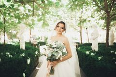 Beautiful brunette bride in elegant white dress holding bouquet posing neat trees stock photography
