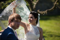 Beautiful brunette bride holding her veil against the sun Royalty Free Stock Image