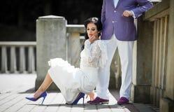 Beautiful brunette bride leaning against stylish groom on balcon Royalty Free Stock Image