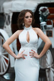 Beautiful brunette bride near horse carriage stock photography