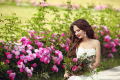 Beautiful brunette bride outdoor portrait. Woman with wedding bo. Uquet of flowers at green park. Makeup.  Attractive young girl model with long wavy hair Stock Image
