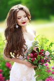 Beautiful brunette bride outdoor portrait. Woman with wedding bo. Uquet of flowers at green park. Makeup.  Attractive young girl model with long wavy hair Stock Photography