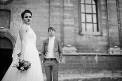 Beautiful brunette bride posing with bouquet, church & groom bac Royalty Free Stock Images