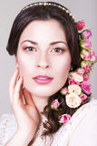 Beautiful brunette bride smiling with natural make up and flowers roses in her hairstyle Stock Photo