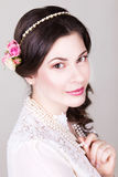 Beautiful brunette bride smiling with natural make up and flowers roses in her hairstyle Stock Photography