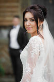 Beautiful brunette bride walking down old street, while the groo Stock Image
