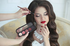Beautiful brunette bride wedding portrait with makeup and hairst. Yle. Red lips and manicure nails. Stylist makes make-up model on wedding day. portrait of young Royalty Free Stock Photography