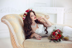 Beautiful brunette Bride wedding Portrait. Red lips makeup. Long. Wavy hair style. Expensive diamond jewelry. Bridal bouquet of flowers. Elegant lady lying on Stock Photography
