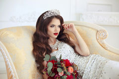 Beautiful brunette Bride wedding Portrait. Red lips makeup. Long. Wavy hair style. Expensive diamond jewelry. Bridal bouquet of flowers. Elegant lady lying on Royalty Free Stock Photo