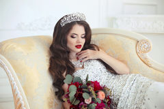 Beautiful brunette Bride wedding Portrait. Red lips makeup. Long. Wavy hair style. Expensive diamond jewelry. Bridal bouquet of flowers. Elegant lady lying on Stock Image