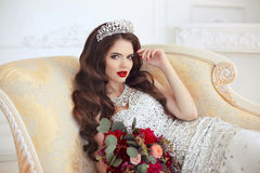 Beautiful brunette Bride wedding Portrait. Red lips makeup. Long. Wavy hair style. Expensive diamond jewelry. Bridal bouquet of flowers. Elegant lady lying on Stock Images