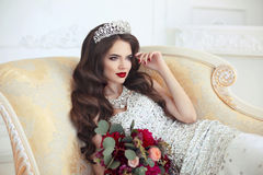 Beautiful brunette Bride wedding Portrait. Red lips makeup. Long. Wavy hair style. Expensive diamond jewelry. Bridal bouquet of flowers. Elegant lady lying on Stock Photo