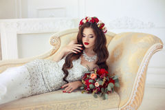 Beautiful brunette Bride wedding Portrait. Red lips makeup. Long. Wavy hair style. Expensive diamond jewelry. Bridal rose bouquet of flowers. Elegant lady lying Royalty Free Stock Photos