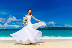 Beautiful brunette bride in white wedding dress with big long wh. Ite train and with wedding bouquet stand on shore sea. Tropical sea in the background. Summer Royalty Free Stock Photos