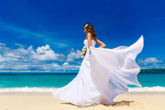 Beautiful brunette bride in white wedding dress with big long wh. Ite train and with wedding bouquet stand on shore sea. Tropical sea in the background. Summer Stock Images