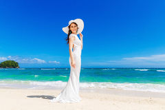 Beautiful brunette bride in white wedding dress and straw hat ha Stock Photos