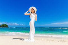 Beautiful brunette bride in white wedding dress and straw hat ha Stock Image