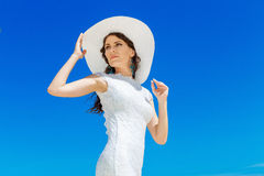 Beautiful brunette bride in white wedding dress and straw hat ha Stock Photo