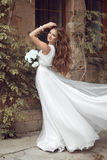 Beautiful brunette bride woman with long wavy hair in luxurious Stock Photo