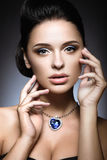 Beautiful brunette with a bright evening make-up with a necklace Heart of the Ocean. royalty free stock photo