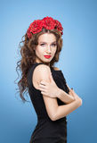 Beautiful brunette with bright red lipstick wearing flower alike Stock Photography