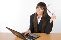 Beautiful brunette business girl. Beautiful brunette businesswoman with glasses working on a laptop computer Stock Photography