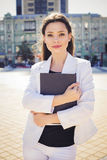 Beautiful brunette business woman in white suit with folder of documents in her hands outdoors Stock Images