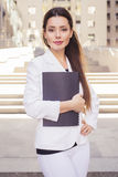 Beautiful brunette business woman in white suit with folder of documents in her hands outdoors Stock Image