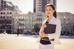 Beautiful brunette business woman in white suit with folder of documents in her hands outdoors Royalty Free Stock Images