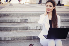 Beautiful brunette business woman in white suit with notebook on her lap, typing, working outdoors. Copy space Royalty Free Stock Photography