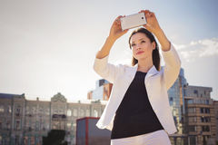 Beautiful brunette business woman in white suit photographing se Stock Photos