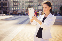 Beautiful brunette business woman in white suit photographing on Royalty Free Stock Photography