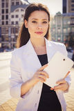 Beautiful brunette business woman in white suit working on a tab Royalty Free Stock Photo