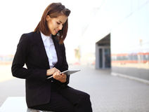 Beautiful brunette business woman working on a tablet Royalty Free Stock Images