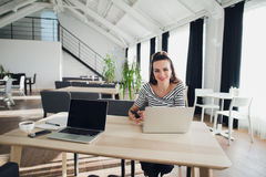 Beautiful brunette businesswoman working, looking at camera and smiling. Attractive woman holding tablet. Elegant style royalty free stock photo