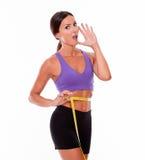 Beautiful brunette calling measuring her waist Royalty Free Stock Photos
