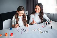 Beautiful brunette caucasian mother and daughter paint together in room. Young woman look at girl and smile. She hold royalty free stock photos